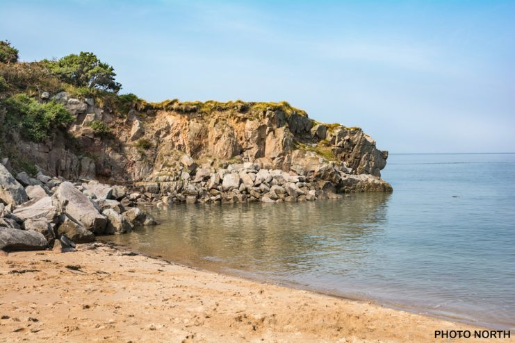 Stock Photo - The small sandy cove beneath the sandstone cliffs of Heysham Head on the Lancashire coast, England, UK.